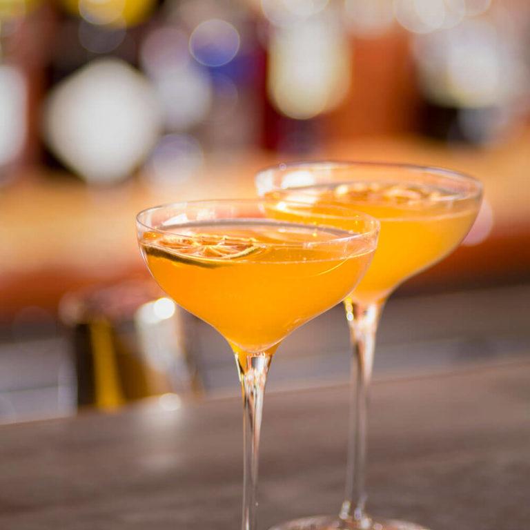 Two orange cocktails on a bar